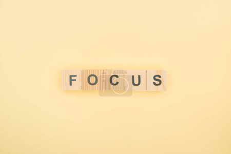 top view of focus lettering made of wooden cubes on yellow background