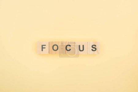 Photo pour Vue du dessus du lettrage de mise au point en cubes de bois sur fond jaune - image libre de droit
