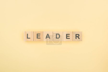 top view of leader lettering made of wooden cubes on yellow background