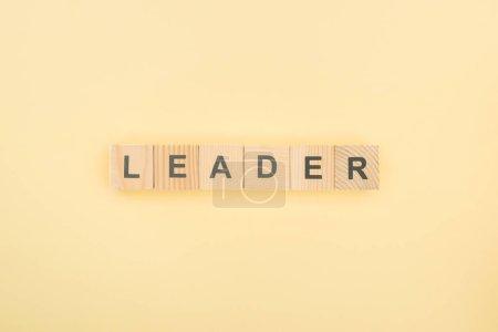 Photo pour Vue du dessus du lettrage de leader en cubes de bois sur fond jaune - image libre de droit
