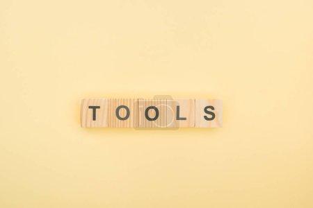 Draufsicht der Werkzeuge Schriftzug aus Holzwürfeln auf gelbem Hintergrund