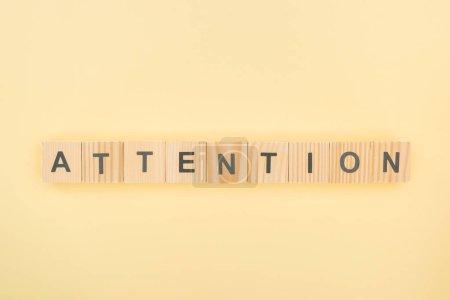 Draufsicht auf Aufmerksamkeitsschriftzug aus Holzwürfeln auf gelbem Hintergrund