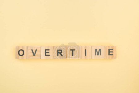 top view of overtime lettering made of wooden cubes on yellow background