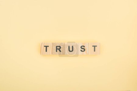 top view of trust lettering made of wooden cubes on yellow background