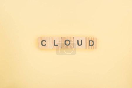 Photo pour Vue de dessus du lettrage de nuage composé de cubes en bois sur fond jaune - image libre de droit