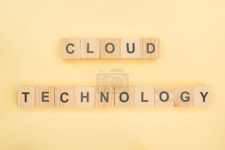 Photo for Top view of cloud technology lettering made of wooden cubes on yellow background - Royalty Free Image