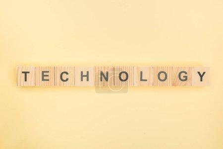 Foto de Vista superior de Letras de la tecnología de cubos de madera sobre fondo amarillo - Imagen libre de derechos