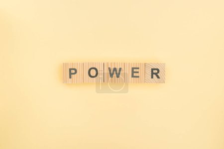 top view of power lettering made of wooden cubes on yellow background