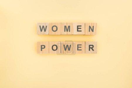 Foto de Vista superior de las mujeres con letras de poder hechas de cubos de madera sobre fondo amarillo - Imagen libre de derechos