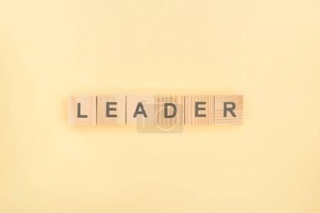 Draufsicht auf Leader-Schriftzug aus Holzwürfeln auf gelbem Hintergrund