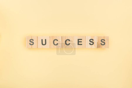 top view of success lettering made of wooden cubes on yellow background