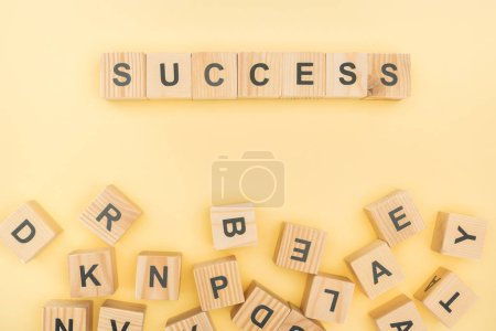 Photo for Top view of success lettering with wooden cubes on yellow background - Royalty Free Image