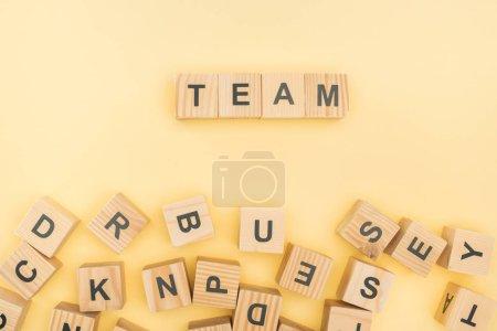 Photo pour Vue du dessus du lettrage d'équipe avec des cubes en bois sur fond jaune - image libre de droit