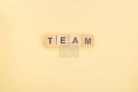 Photo pour Vue du dessus du lettrage d'équipe en cubes de bois sur fond jaune - image libre de droit