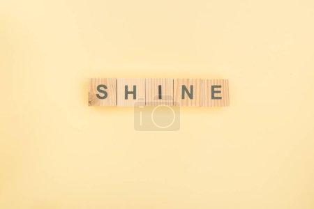 Photo pour Vue de dessus du lettrage de brillance faite de cubes en bois sur fond jaune - image libre de droit