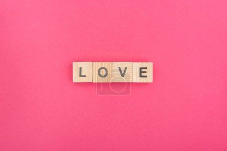 Photo pour Vue du dessus des lettres d'amour en blocs de bois sur fond rose - image libre de droit
