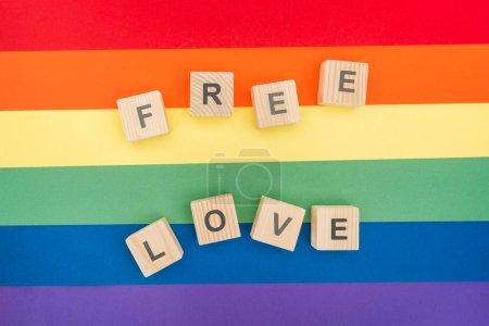 Photo pour Vue de dessus des lettres d'amour libre faite de cubes en bois sur fond de papier arc-en-ciel - image libre de droit