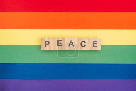 Photo pour Vue de dessus de pease lettrage paix faite de cubes en bois sur fond de papier arc-en-ciel - image libre de droit
