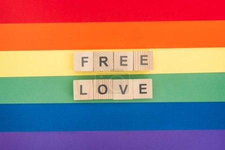 Photo pour Vue de dessus des lettres d'amour libre constitué de blocs en bois sur fond de papier arc-en-ciel - image libre de droit