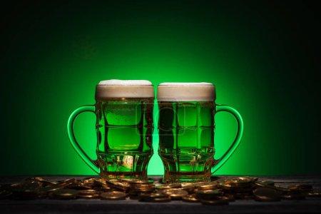 Photo pour Verres de bière alcoolisée debout près de pièces d'or sur st patricks jour sur fond vert - image libre de droit