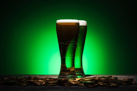 Photo for Glasses of green beer standing near golden coins on green background - Royalty Free Image