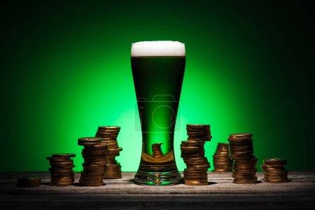 Photo pour Verre de bière irlandaise se tenant debout sur une table en bois près de pièces d'or sur fond vert - image libre de droit