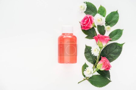 Photo for Top view of flowers composition and bottle with orange lotion isolated on white - Royalty Free Image