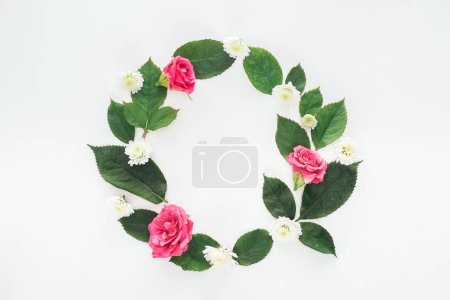 top view of circular composition with green leaves, roses and chrysanthemums isolated on white