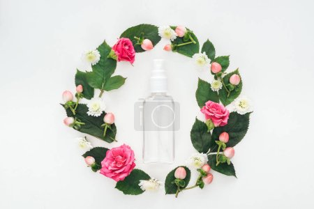 Photo for Top view of circular composition with green leaves, flowers and empty spray bottle isolated on white - Royalty Free Image