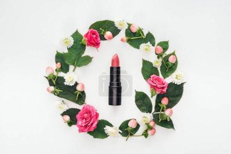 Photo pour Vue de dessus de composition circulaire avec des feuilles vertes, fleurs et rouge à lèvres rose isolé sur blanc - image libre de droit
