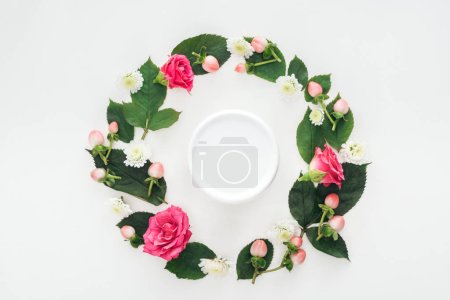 Photo pour Vue de dessus de composition circulaire avec feuilles, fleurs et beauté crème isolé sur blanc - image libre de droit