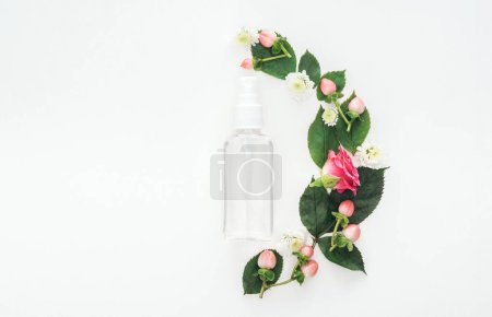 Photo for Top view of composition with leaves, flowers and empty spray bottle isolated on white - Royalty Free Image