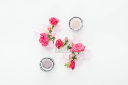 Photo for Top view of composition with roses buds, berries, petals and cosmetic bottles on white background - Royalty Free Image