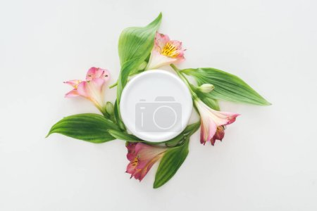 Photo pour Vue de dessus de composition de fleurs et de beauté crème en bouteille sur fond blanc - image libre de droit