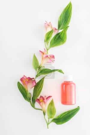 Photo pour Vue de dessus de la composition avec alstroemeria rose fleurs, de feuilles vertes et de bouteille de lotion orange sur fond blanc - image libre de droit