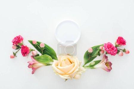 Photo pour Vue de dessus de la composition avec crème de beauté, des roses, des baies et des alstroemeria en bouteille sur fond blanc - image libre de droit