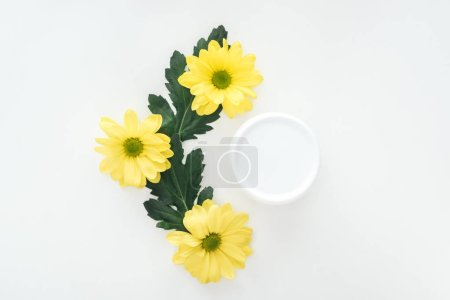 Photo for Top view of composition with yellow chrysanthemums and beauty cream in bottle on white background - Royalty Free Image