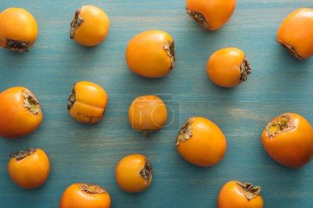 Foto de Vista superior de caquis maduros todo naranja sobre fondo azul - Imagen libre de derechos