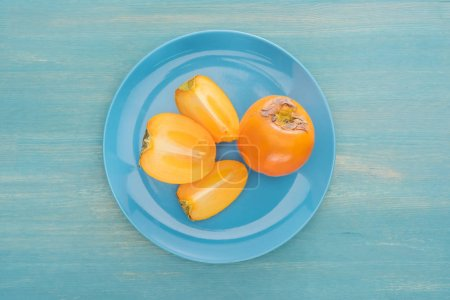 top view of cut and whole ripe persimmons on blue glass plate