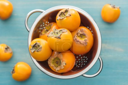 Photo for Selective focus of whole and ripe persimmons in colander on blue background - Royalty Free Image