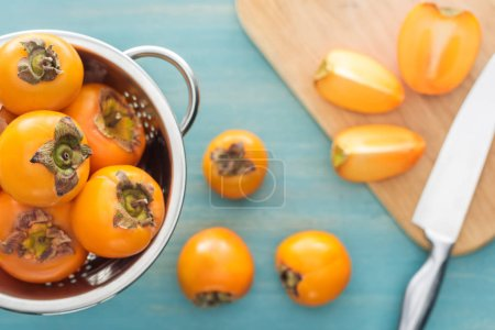 Photo for Selective focus of orange whole persimmons in colander and slices on cutting board - Royalty Free Image