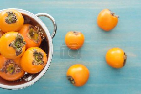 Photo pour Mise au point sélective de juteux kakis orange dans une passoire sur fond bleu - image libre de droit