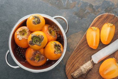 Photo for Top view of orange persimmons in colander and slices on cutting board with knife - Royalty Free Image
