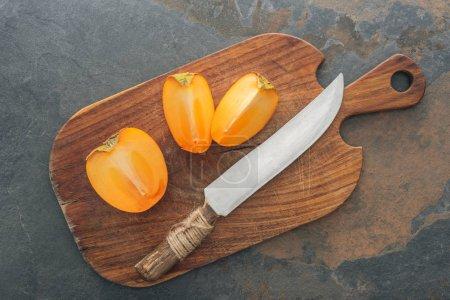 Photo pour Couper les mûres délicieux kakis sur planche à découper avec couteau - image libre de droit
