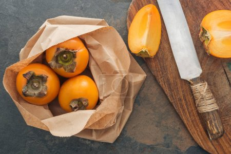 top view of whole persimmons in paper packet and sliced on cutting board
