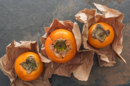vista superior de caquis naranjas maduras enteras en papel