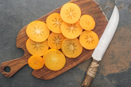Photo for Top view of sliced orange persimmons on cutting board with knife - Royalty Free Image
