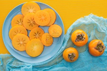 Photo pour Vue de dessus des tranches d'orange kakis sur plaque d'immatriculation bleue - image libre de droit