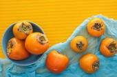 """Постер, картина, фотообои """"вид сверху всего оранжевый хурма на синюю тарелку и ткани"""""""