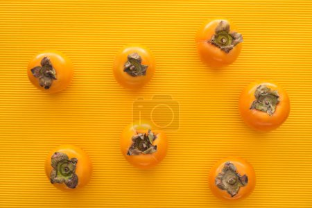 Photo for Top view of whole orange persimmons on yellow background - Royalty Free Image